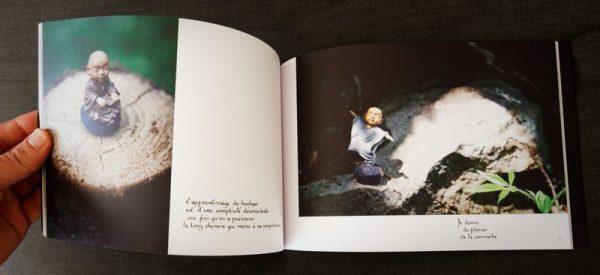 Photo d'une double-page du livre. Sur chaque page, une photo de petit moine et une phrase calligraphiée.