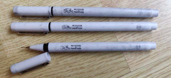Trois crayons Winsor & Newton (tailles 1.0, 0.5 et 0.3). Le capuchon ouvert de l'un d'eux permet de voir une pointe fine, ronde, noire.