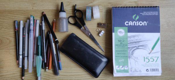Des crayons, du matériel (pot d'eau, ciseaux, scotchs, pince, taille-crayon), aquarelle et carnet de croquis